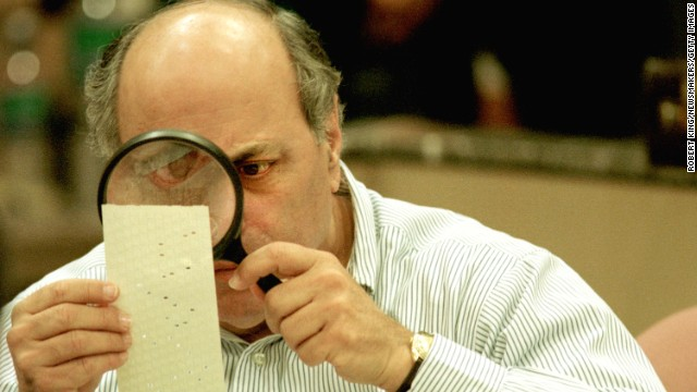 (FILE PHOTO) Judge Robert Rosenberg of the Broward County Canvassing Board uses a magnifying glass to examine a dimpled chad on a punch card ballot November 24, 2000 during a vote recount in Fort Lauderdale, Florida. On May 4, 2001 the Florida state legislature overwhelmingly passed a voting reform act designed to eliminate the controversial punch card ballots which were the focal point of recount efforts in the 2000 presidential election. (Photo by Robert King/Newsmakers)