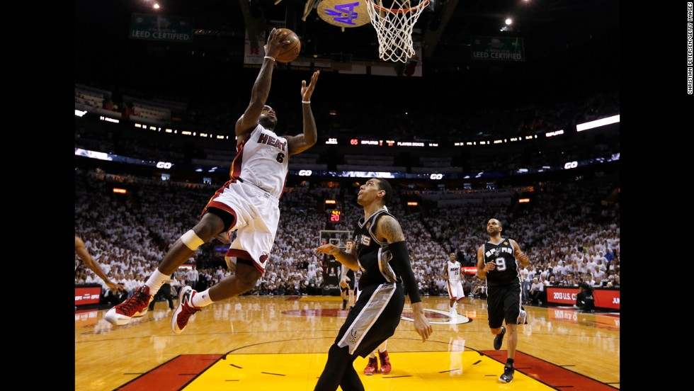 LeBron James of the Miami Heat goes up for a shot against Danny Green of the San Antonio Spurs.
