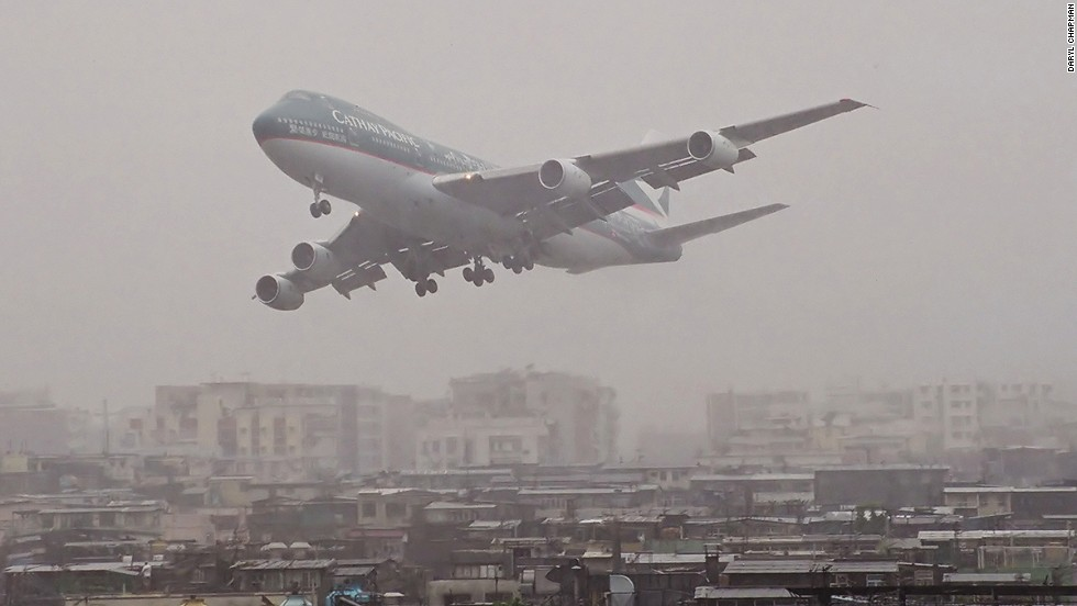 """Watching planes landing in heavy rain is one of Chapman's scariest memories.""""Here's a CX 747-200 getting a little low in the rain,"""" says the photographer. """"Some [pilots] seemed to wait a little longer than others before they aborted the landing and went around for another go. Some would appear out of the low clouds on the approach path then power up and vanish back into the clouds."""""""