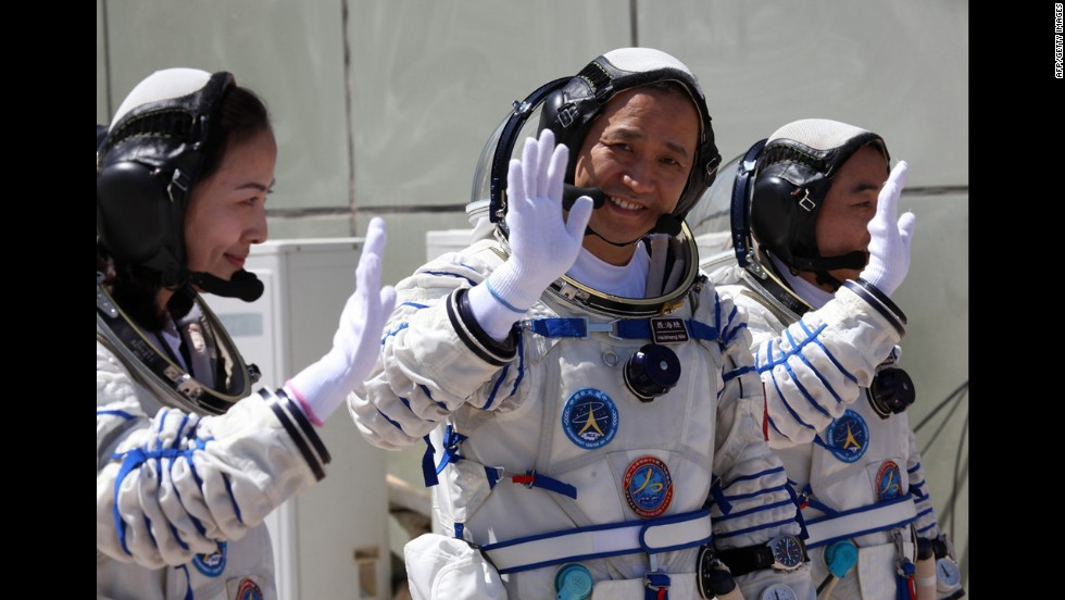 Chinese astronaut Wang Yaping, left, mission commander Nie Haisheng and Zhang Xiaoguang wave to onlookers as they prepare to board on June 11.
