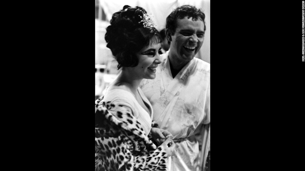 Elizabeth Taylor and Richard Burton share a laugh on the set of 'Cleopatra', Rome, 1962.