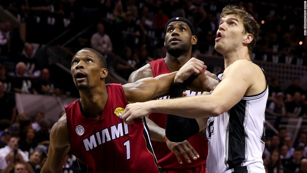Chris Bosh, left, and LeBron James, center, of the Miami Heat box out Tiago Splitter of the San Antonio Spurs.