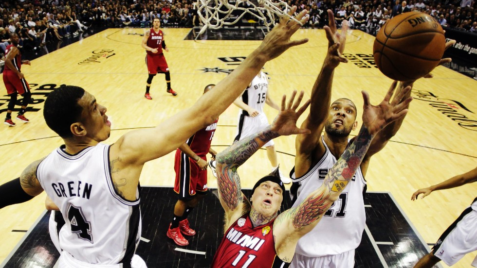 Miami's Chris Andersen goes for a rebound against the San Antonio Spurs' Tim Duncan, right, and Danny Green, left.