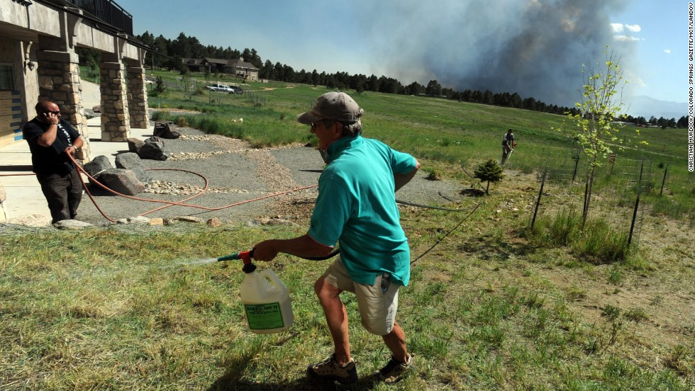 Lynd Fitzgerald sprays fire retardant around a house in Colorado Springs on June 11.