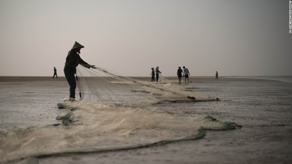 "JUNE 13 - BEIHAI, CHINA: Fishermen pull their nets on Silver beach in Beihai, southwestern China. One of the world's fastest growing cities, the ancient port of Beihai was historically a major trade hub. As China's urban population expands, the traditionally rural, agriculture-focused country is facing its <a href=""http://cnn.com/2012/01/20/world/asia/china-florcruz-urban-growth"">biggest social change ever</a>."
