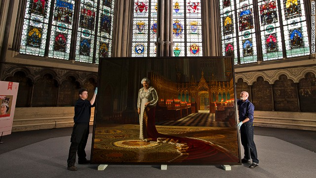 Momart employees hold a portrait of Queen Elizabeth II before it is moved inside Westminster Abbey on May 17, 2013 in London.