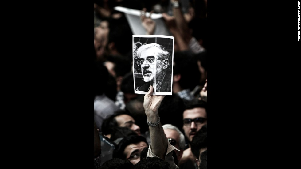 "A man holds a portrait of opposition leader Mir Hossein Mousavi, who has been <a href=""http://www.cnn.com/2011/WORLD/meast/02/19/iran.opposition.leader/index.html"">under house arrest since February 2011</a>, during a campaign rally for Aref in Tehran on June 10."