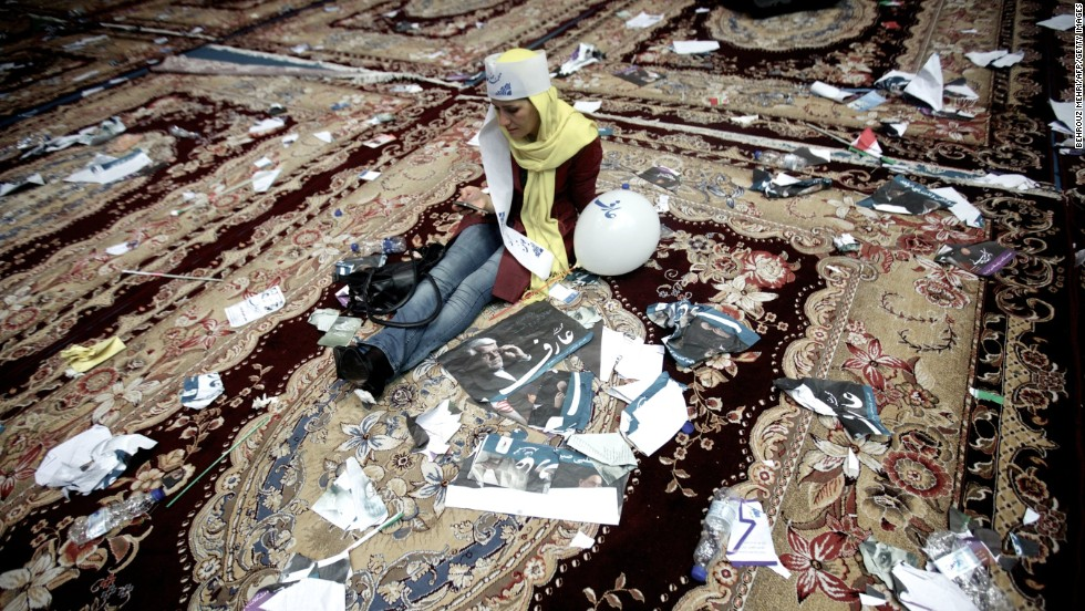 An Aref supporter checks her mobile phone surrounded by campaign posters after the June 10 rally in Tehran.