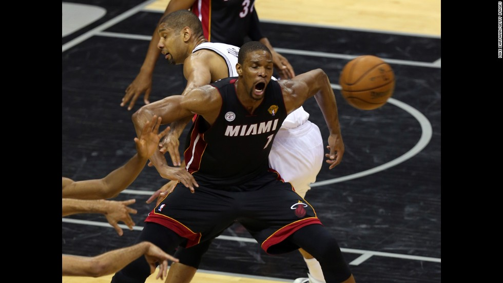 Chris Bosh of the Miami Heat battles for the ball against Tim Duncan of the Spurs in the first half.