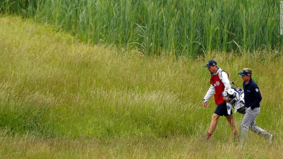 Luke Donald of England walks with caddie John McLaren on the 17th hole on June 14.
