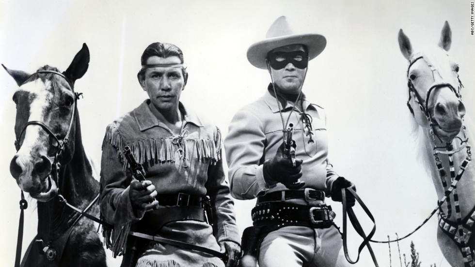 The Lone Ranger, played by Clayton Moore, right, and his Native American partner, Tonto, played by Jay Silverheels, pose with their trusty steeds.