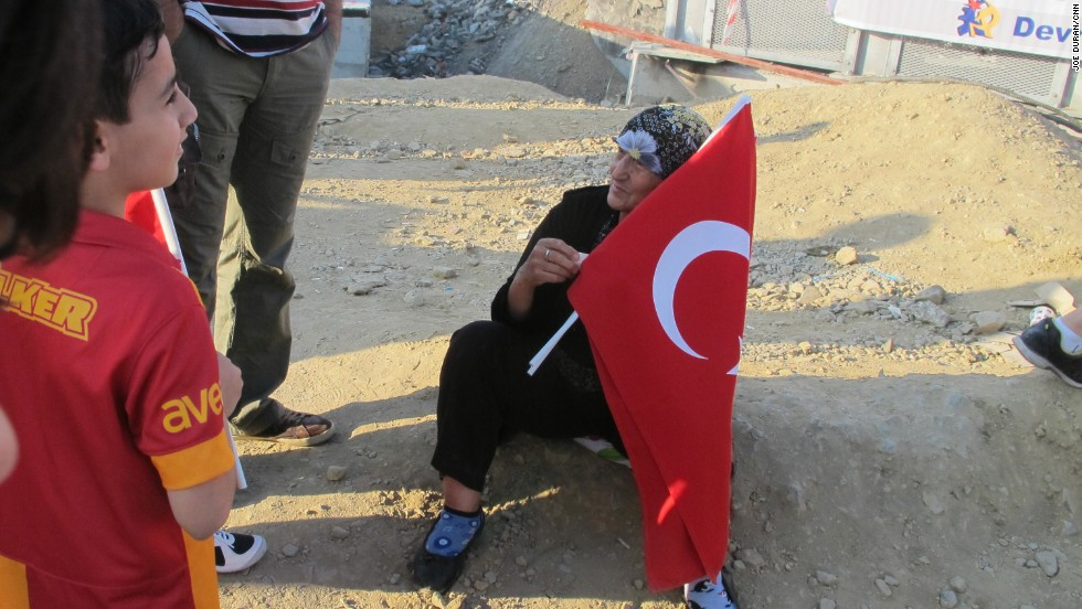 A woman in Taksim Square in Istanbul sells Turkish flags on Saturday, June 7, 2013 to visitors and protesters.