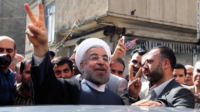 Iranian presidential candidate, Hassan Rohani flashes a victory sign as he leaves a polling station after voting in Tehran on June 14, 2013.