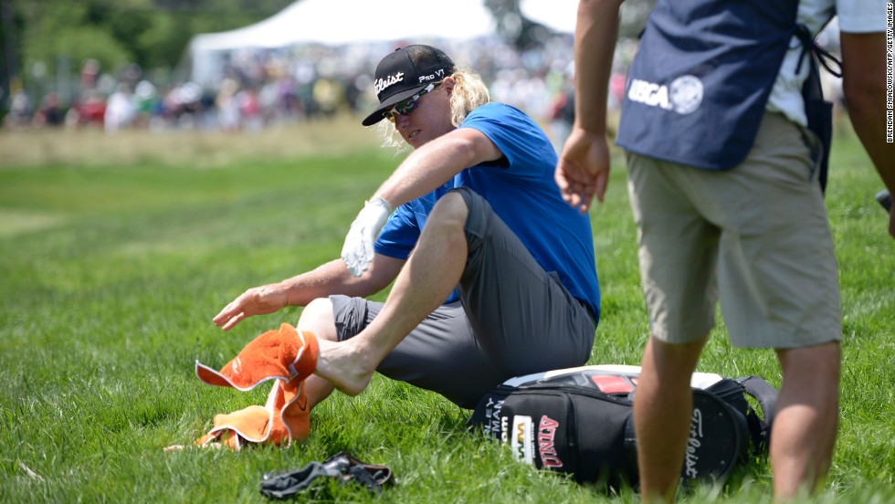 Charley Hoffman dries his feet after chipping to the fourth green from a creek  during the third round on June 15.