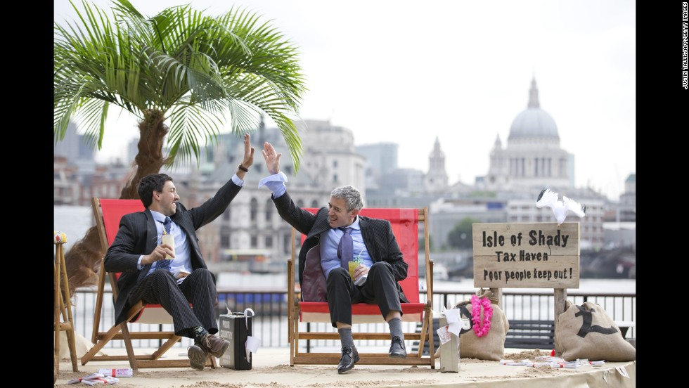 "Protesters in suits high-five on the set of their ""Isle of Shady Tax Haven"" in London on Friday, June 14."