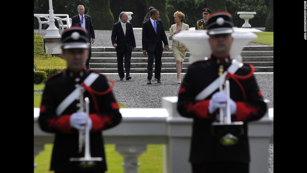 Obama walks flanked by Irish President Mary McAleese, right, and her husband, Martin McAleese, as they arrive at the President's Residence to plant a tree in Dublin on May 23, 2011.