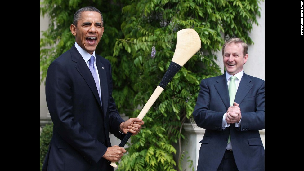 Obama poses for pictures with an Irish hurling stick, as Irish Prime Minister Enda Kenny looks on in Dublin on May 23, 2011.