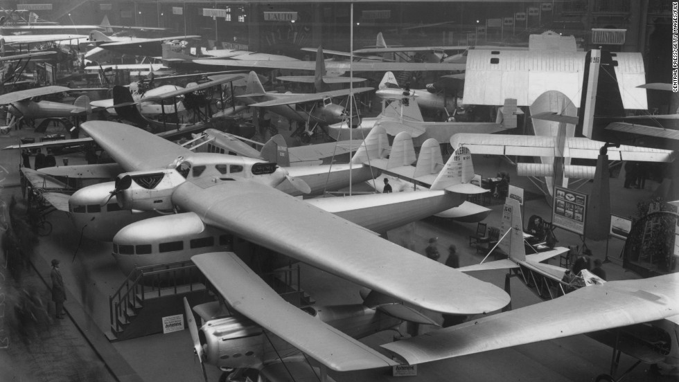 A Bleriot XII is displayed under a Bleriot 125 at the 1930 Paris Airshow. In the foreground, you can see a SPAD 91 biplane.