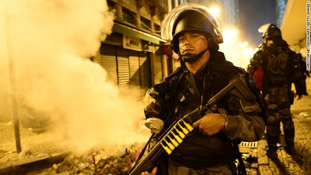 A riot police officer holds a weapon during clashes in Rio de Janeiro's downtown, on June 17, 2013.