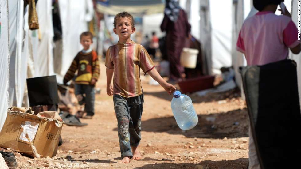 A boy carries a jug for water at the Maliber al-Salam refugee camp in April 2013. The camp, near the Turkish border, houses internally displaced Syrian families.