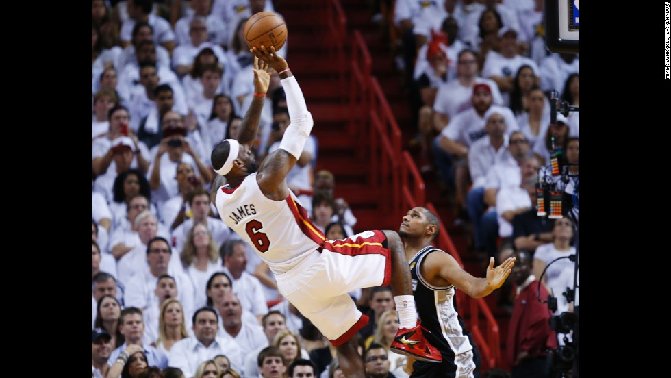 Miami Heat's LeBron James takes a fade-away jumper while being guarded by San Antonio Spurs' Boris Diaw.