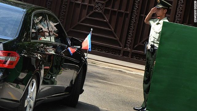 A Chinese officer salutes the car of North Korean officials as they return from talks in Beijing on June 19, 2013.