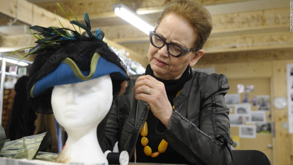"White works on a hat for Elizabeth. ""I fall in love with every garment as its being made,"" she said."