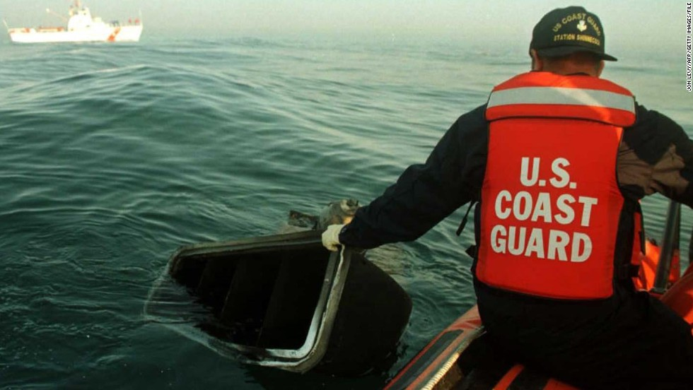 A member of the U.S. Coast Guard pulls a piece of wreckage from the waters on July 18, 1996.