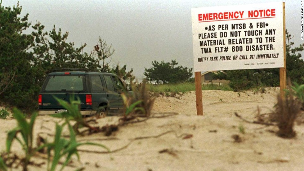 A warning sign on the dunes alerts beach-goers to watch for debris washed ashore at Smith's Point, Long Island, New York, on July 25, 1996.