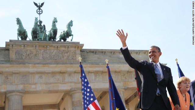 US President Barack Obama (L) waves next to German Chancellor Angela Merkel (R) before they deliver speeches to invited guests in front of the Brandenburg Gate at Pariser Platz in Berlin, on June 19, 2013, during the official visit of the US President. Barack Obama walks in John F. Kennedy's footsteps on his first visit to Berlin as US president, but encounter a more powerful and sceptical Germany in talks on trade and secret surveillance practices.  AFP PHOTO / POOL / MICHAEL KAPPELER        (Photo credit should read MICHAEL KAPPELER/AFP/Getty Images)