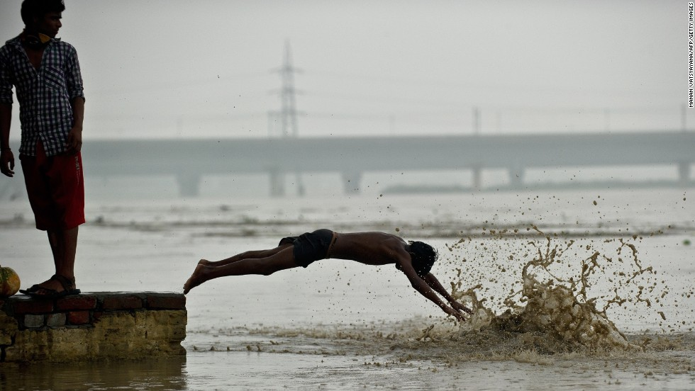 "JUNE 19, NEW DELHI, INDIA: A youth dives into the rising waters of the Yamuna river in New Delhi on June 18. <a href=""http://cnn.com/2013/06/18/asia/gallery/india-monsoon/?hpt=ias_t2"">Monsoon rains have arrived early in the north of the country, </a>leaving at least 64 people dead and thousands stranded, officials said June 18."