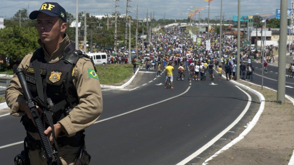A police officer holds his weapon as protesters continue their demonstration ahead of Brazil's Group A match with Mexico in the ongoing Confederations Cup.