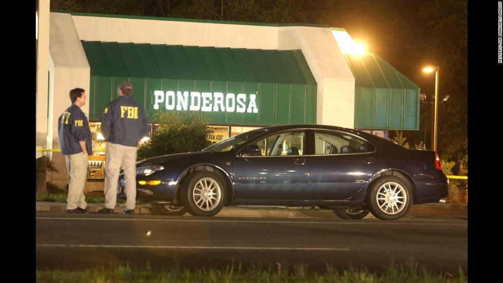 Two FBI agents stand in front of a Ponderosa restaurant in Ashland, Virginia, where Jeffrey Hopper was shot on October 19, 2002. The 37-year-old was shot in the stomach while walking with his wife in the parking lot. He survived.