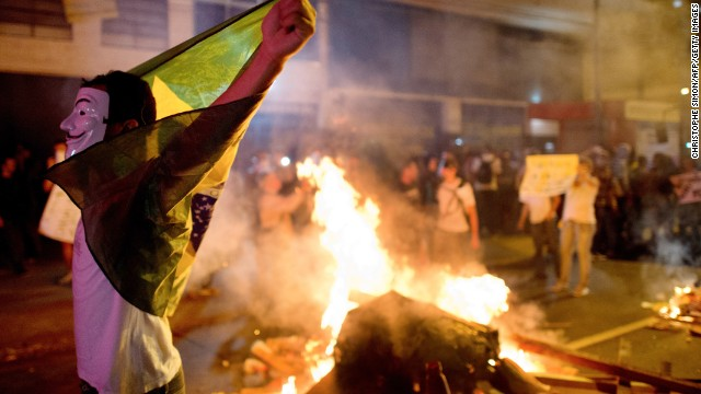 A demonstrator holds a flag late on June 19, 2013 during clashes in the center of Niteroi, 10 kms from Rio de Janeiro. Protesters battled police late on June 19, even after Brazil's two biggest cities rolled back the transit fare hikes that triggered two weeks of nationwide protests. The fare rollback in Sao Paulo and Rio de Janeiro marked a major victory for the protests, which are the biggest Brazil has seen in two decades. AFP PHOTO / CHRISTOPHE SIMON (Photo credit should read CHRISTOPHE SIMON/AFP/Getty Images)