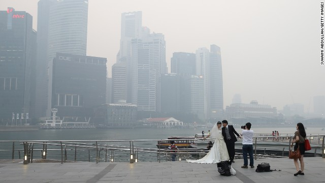SINGAPORE - JUNE 20: A couple takes a pre-wedding photographs as the city skyline is filled with smog at the Marina Bay Waterfront on June 20, 2013 in Singapore. The Pollutant Standards Index (PSI) rose to the highest level on record reaching 371 at 1pm. The haze is created by deliberate slash-and-burn forest fires started by companies in neighbouring Sumatra. (Photo by Suhaimi Abdullah/Getty Images)