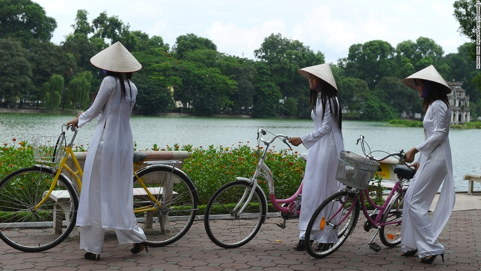 "<strong>Hoan Kiem Lake: </strong>Young girls wear traditional conical hats and ""ao dai"" dresses in honor of a celebration at Hoan Kiem Lake, a popular hangout for locals. The lake is a stop during the eBuddies half-day tour."