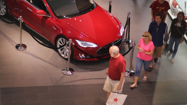 People walk out of a Tesla motor company dealership in the Dadeland Mall on June 6, 2013 in Miami.