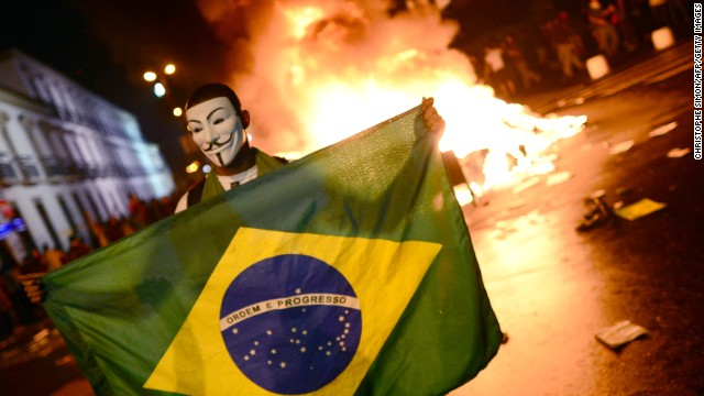 A demonstrator wearing a Guy Fawkes mask holds a Brazilian national flag during clashes in downtown Rio de Janeiro on June 17, 2013, after a protest against higher public transportation fares and the use of public funds to finance international football tournaments. Protesters in several major cities are up in arms over hikes in mass transit prices -- from $1.5 to $1.6 -- as well as over the $15 billion earmarked for the two sports events amid calls for more health and education funding.