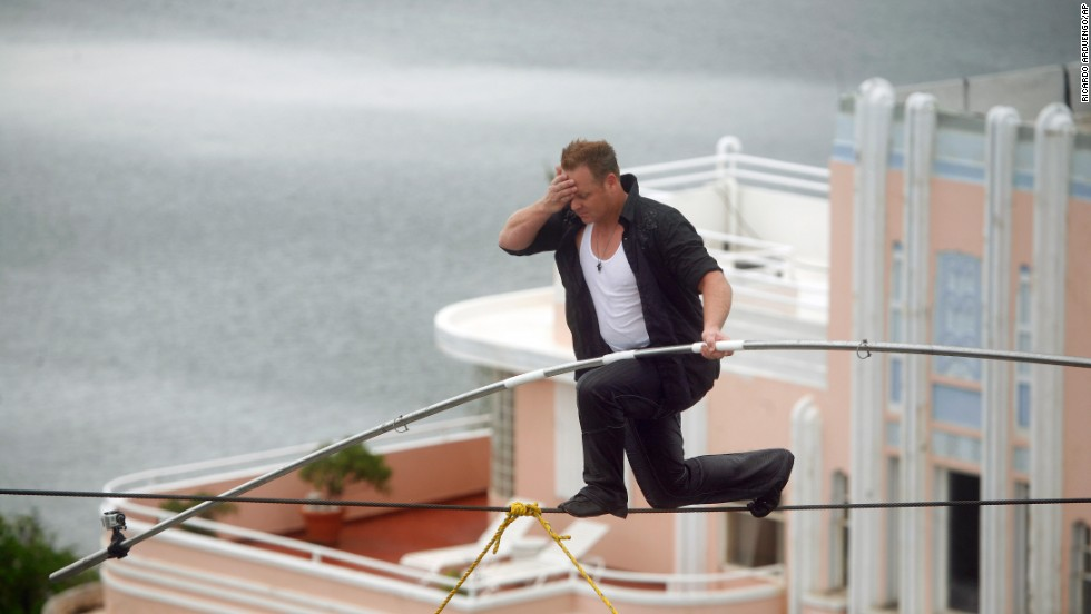 Wallenda wipes sweat from his forehead as he maneuvers across a 300-foot-long wire suspended 100 feet in the air between two towers of Puerto Rico's Conrad San Juan Condado Plaza Hotel in June 2011.
