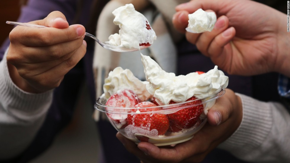 Spectators enjoy a bowl of strawberries and cream on June 24 during Wimbledon at the All England Lawn Tennis and Croquet Club in London.