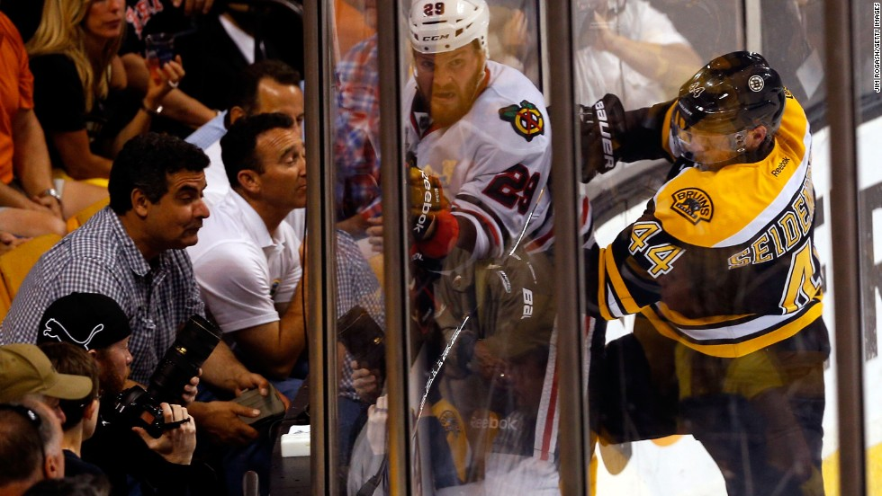 Dennis Seidenberg of the Boston Bruins checks Bryan Bickell of the Chicago Blackhawks.