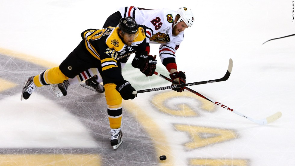 Daniel Paille of the Boston Bruins skates for the puck against Bryan Bickell of the Chicago Blackhawks.