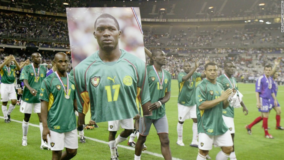 Cameroonian players join 2003 Confederations Cup champions France on a lap of honor, bearing an image of Foe -- whose medal is hanging off his portrait.