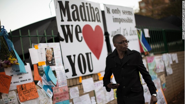 A well wisher walks in front of a wall covered with messages to the ailing former South African president Nelson Mandela in Pretoria June 26, 2013. Nelson Mandela's close family members gathered to hear a sombre prayer wishing the anti-apartheid icon a 'peaceful, perfect, end' as he lay in hospital in a critical condition with life seemingly slipping away.