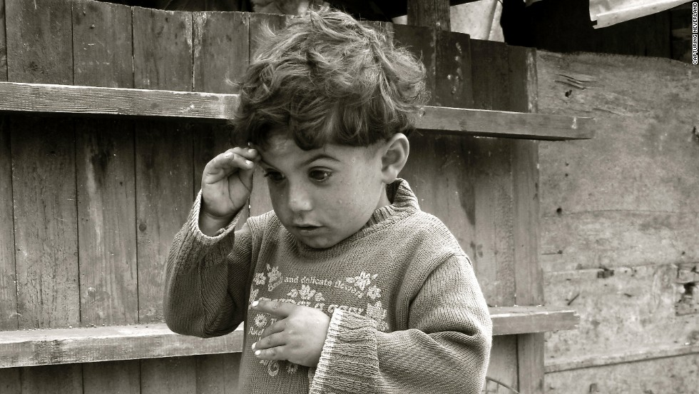 "This black-and-white image called ""The Underprivileged Genius"" was taken by a boy named Claude, 15, in Lebanon. It features a boy with a shocked look on his face -- as if he's trying to process something he doesn't understand. His sweater is emblazoned with a phrase that includes the word ""delicate."""