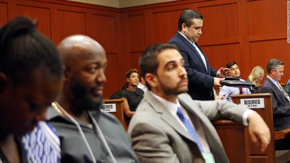 Zimmerman walks past Martin's parents, Sybrina Fulton, left, and Tracy Martin, second from left, as he enters the courtroom after lunch recess on June 26.