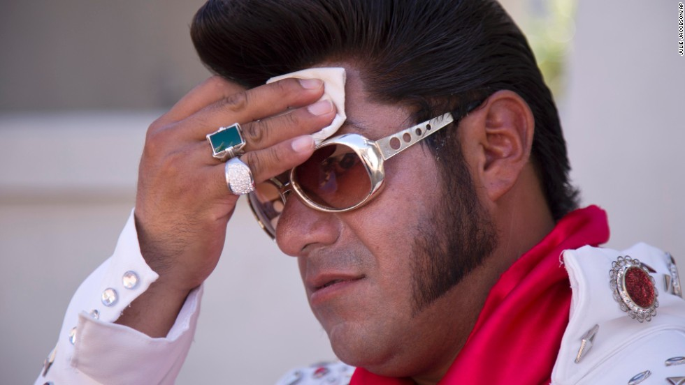 Elvis impersonator Cristian Morales wipes sweat from his brow while posing for photos with tourists on the Las Vegas Strip on Thursday, June 27.