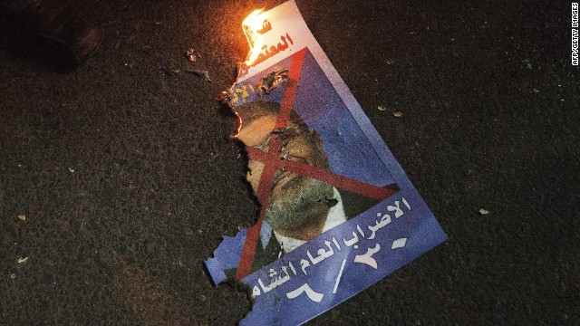 A picture of Egyptian President Mohammed Morsi burns on the ground as anti-government protesters demonstrate on June 26, 2013 in Cairo, Egypt.