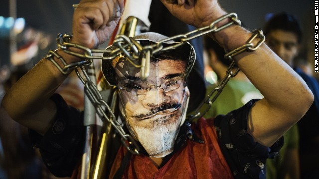 A chained protester wearing a picture of Egyptian President Mohamed Morsy Morsi poses in Tahrir Square on June 26, 2013 in Cairo, Egypt.