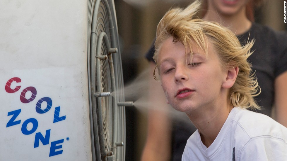 Easton Martin, 10, stops to cool off with a misting fan in Las Vegas with his family on June 28.
